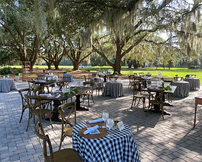 Tables set with charming gingham tablecloths in the courtyard with trees surrounding