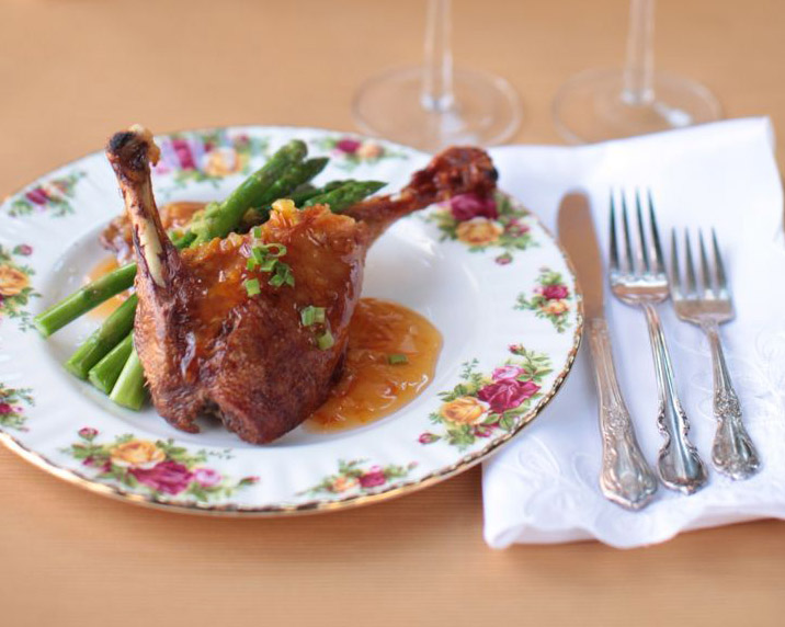 glazed chicken leg with green beans on a china plate