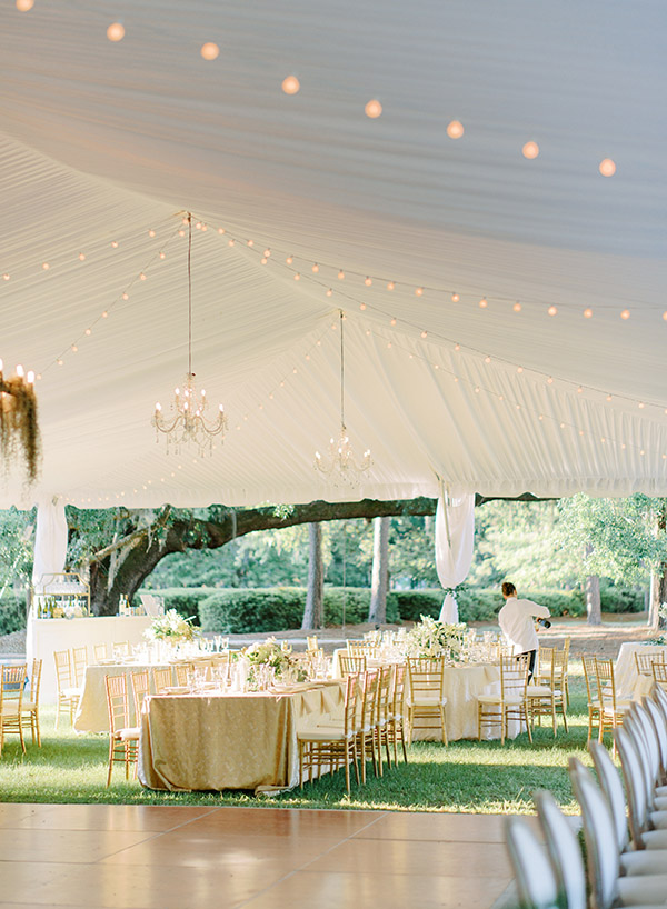 Elegant tented wedding reception with tables set and a server pouring the champagne