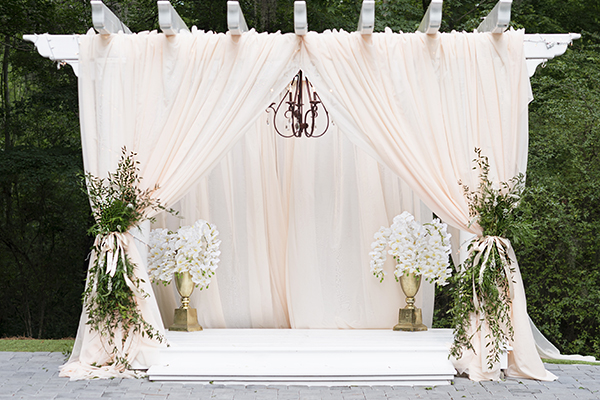 white pergola with blush pink draping and greenery sprays to create a beautifully designed wedding altar