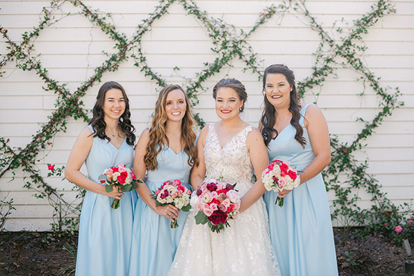 Bride and bridesmaids in blue dresses holding bright pink bouquets with a lattice of vines in the background