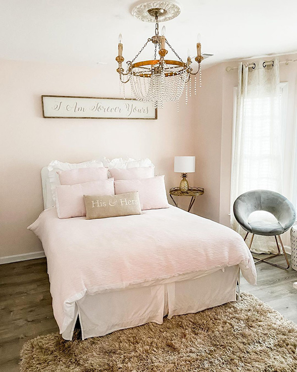 Feminine bedroom in hues of blush, gold, and grey with a queen size bed and chandelier