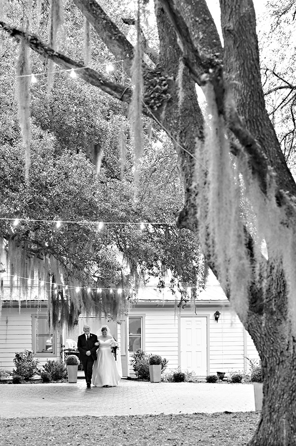 Bride and her father walking out of a white building with live oak trees and spanish moss in the foreground