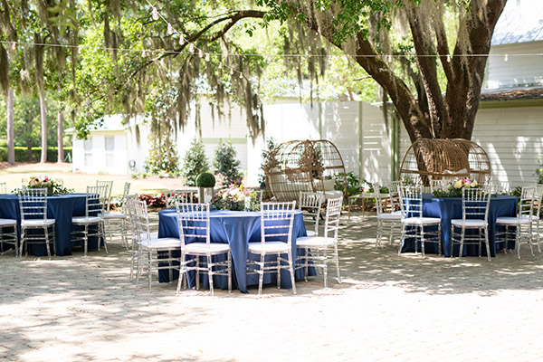 Outdoor courtyard shadowed by graceful live oaks with tables and chairs set up for a wedding reception