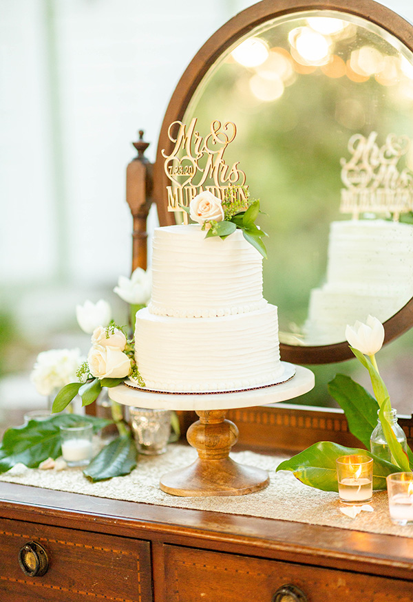 Two-tier wedding cake on a wooden cake stand sitting on a vintage wash stand with mirror