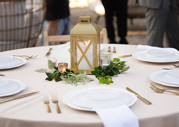 Gold lantern surrounded by greenery in the center of a table set with white china and gold flatware