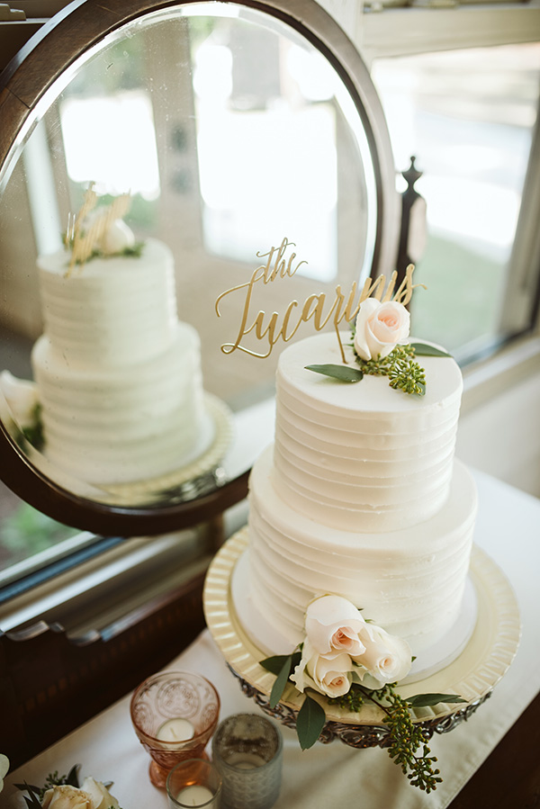 Two-tier white wedding cake with roses and greenery