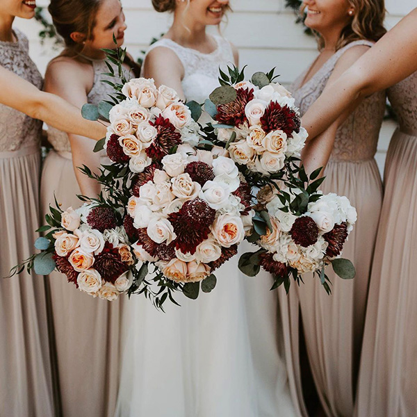 Bridesmaids holding out bouquets with burgundy and blush wedding colors