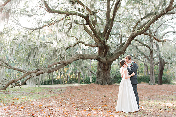 Bride and groom kiss in front of a huge live oak tree