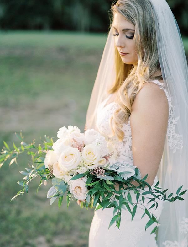 bride holding bouquet of white roses and greenery with golden hour sunlight