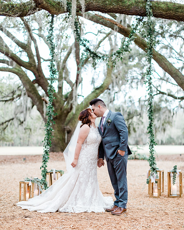 Bride and Groom kissing under the oak trees with lantern decor and greenery garland