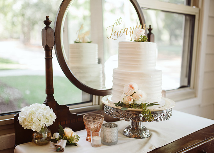 white 2-tier wedding cake with horizontal texture and pale pink rose decor