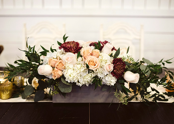 floral arrangement featuring burgundy, pink, and white flowers on a wedding reception table