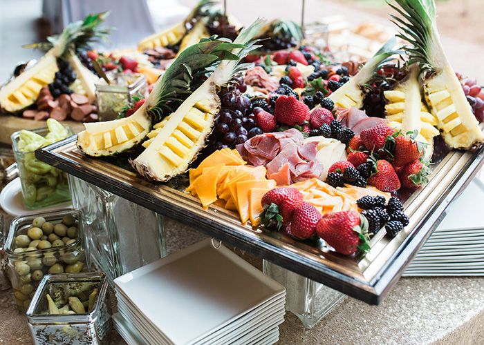 a bountiful display of pineapples, berries, meats, and cheeses arranged for a charcuterie display at a Lowcountry wedding reception