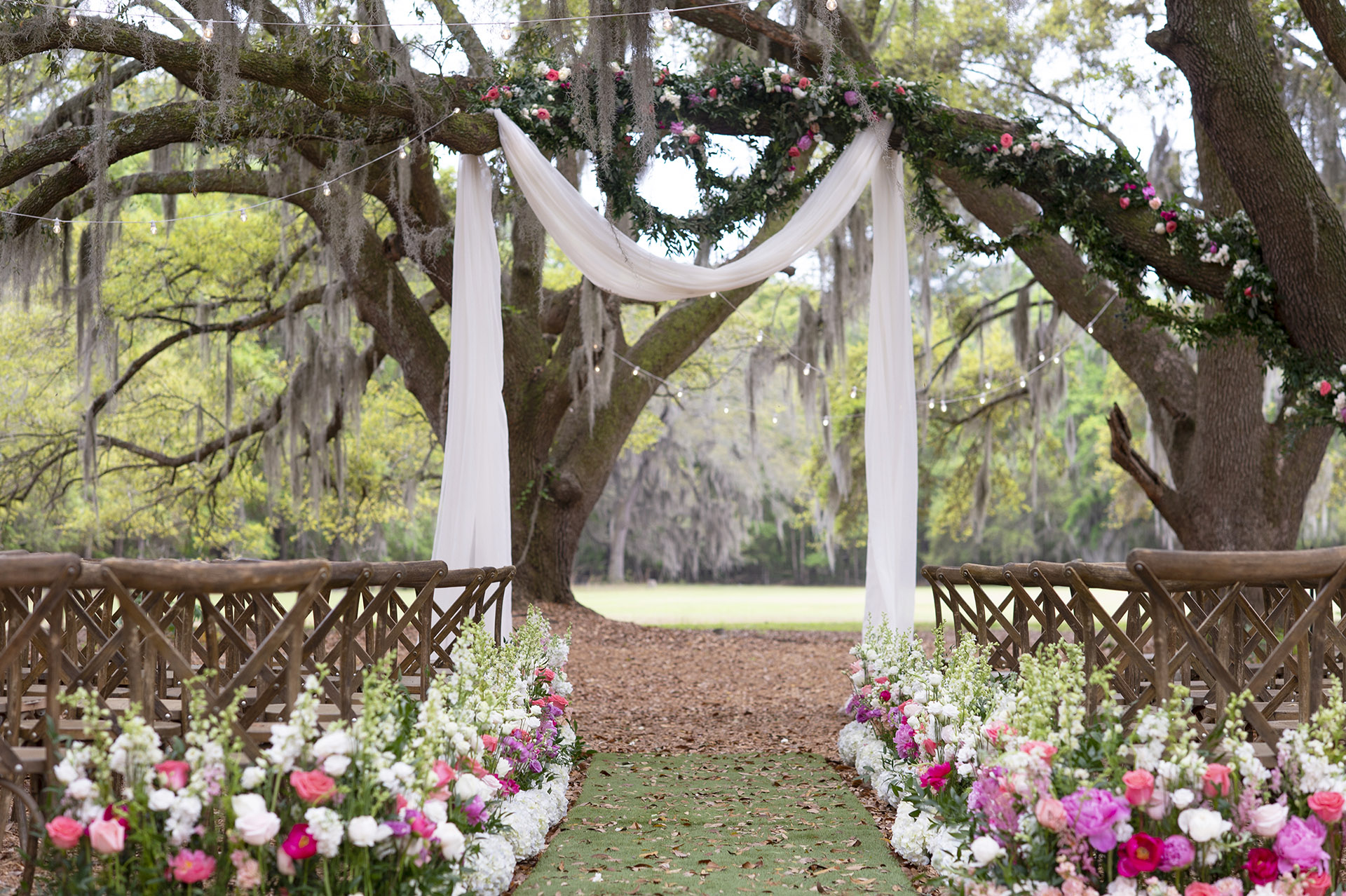 Angel Oak Canopy wedding ceremony with white chiffon draping at the altar and the aisle lined with pink and white spring florals