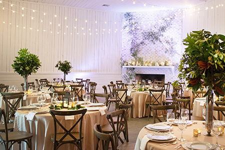 Round tables with chiavari chairs set up for an elegant wedding reception in Gracie Ballroom at Hewitt Oaks in Bluffton, SC