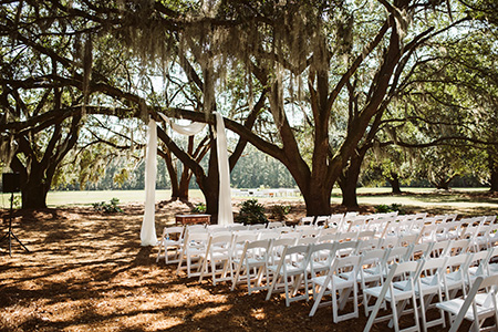 white chairs and elegant chiffon draping set up for an outdoor wedding ceremony under the Angel Oak Canopy at Hewitt Oaks in Bluffton, SC