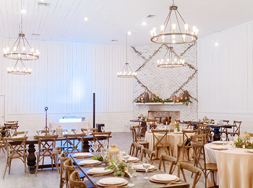Gracie Ballroom at Hewitt Oaks with double height ceilings lit with modern style chandeliers and tables decorated with florals