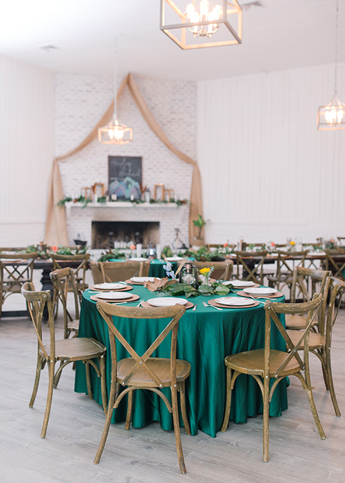 spacious Gracie Ballroom set up for a wedding reception with round tables and chiavari chairs featuring a teal and tan color palette