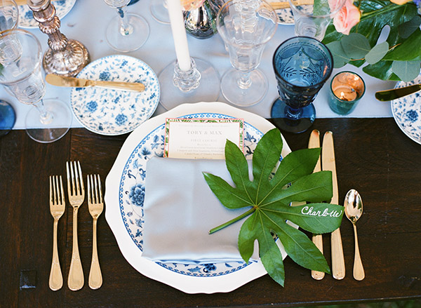 place setting with blue and white china, baby blue linens, and tropical leaf placecard