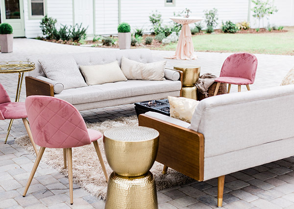 seating area with mid-century modern couches and chairs in neutral linen and pink velvet with wood and gold accents